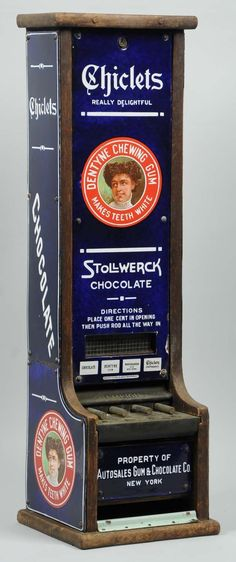 Antique Stollwerck and Chiclets vending machine designed to dispense both chocolate candy and chewing gum; porcelain with wood back.