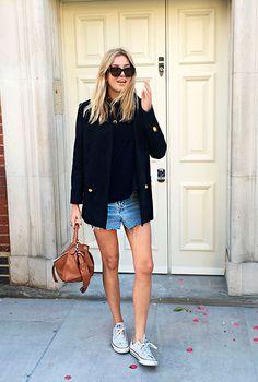 Street style look com shorts jeans e blusa preta mais blazer social preto e tênis branco