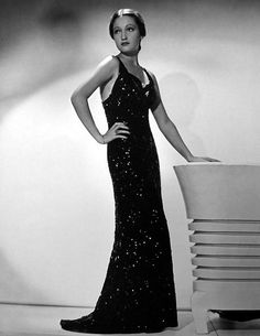 """""""Sequins are particularly suitable for this black evening gown worn by Dorothy Lamour. The slim, slinky lines of the gown plus the glittering black pailettes spell smartness and extreme sophistication. At top of the bodice an arrow of rhinestones serves as a highlight.""""  Dorothy Lamour,1937."""