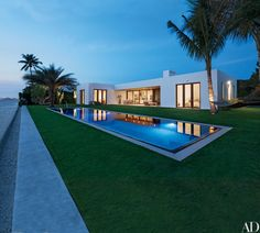 An evening view of the property. Klein, 1100 Architect, and landscape architect Steven Marc Dauber collaborated on the spare scheme, featuring palm trees placed like sculptures around the European-edge pool, which is framed by limestone coping | archdigest.com