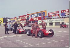 "Works mechanics wheel out car #20 Phil Hill's F1 Dino (the future Pat Hoare car) for the start of the 1960 Italian Grand Prix at Monza. Car #22 is the developmental rear-engined car for count Wolfgang von Trips.  Car #22 is the Ferrari which won the Formula Two class in the race after being ""towed"" in the slipstream of the faster F1 Ferraris.  The race, held on a combined Monza road circuit and banked oval, was boycotted by major British teams protesting at the use of the curved banking."