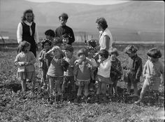 """A Shavuot gathering?  Original caption: The Keren Hayesod. Agricultural Colonies on Plain of Esdraelon  """"The Emek [Jezre'el]."""" Zionist children at play. A spring group. Children picking wild flowers [Library of Congress, circa 1920-1933]"""