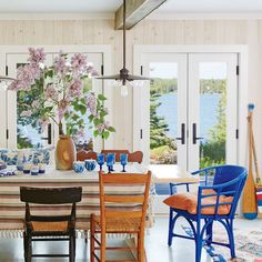 By joining the once-petite living and dining rooms, homeowners created an open, 25- by 35-foot lake-facing living area. Lighter finishes throughout—such as pale gray painted floors and ivory beadboard ceilings—reflect sunlight and brighten the rooms. | Coastalliving.com