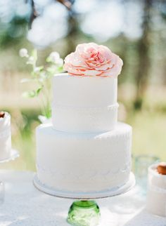 Detailed piping and a blooming flower take a small cake to new heights.