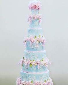 DREAMY PASTEL BLUE wedding cake with pink sugarflowers and lace detail. #weddingcake #tallweddingcakes #pastelweddingcake…
