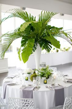 An elegant look for a beach wedding. Tall summer centerpieces with tropical palm leaves surrounded by green votives and small potted ferns. diy centerpieces summer Breathtaking Ideas for Summer Centerpieces: Easy to DIY! Tropical Home Decor, Modern Tropical, Tropical Interior, Tropical Furniture, Tropical Colors, Tropical Leaves, Tropical Centerpieces, Table Centerpieces, Centerpiece Ideas