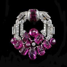 Art Deco clipbroche in tutti-fruttistijl.Platina en witgoud, bezet met diamanten in verschillende slijpvormen en gekerfde robijnen. Gesigneerd: Mauboussin FranceCa. 1925  Afm.:...