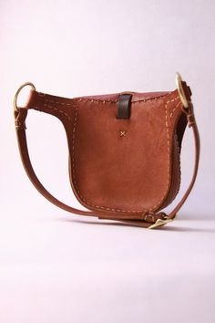 This artisan leather hip bag is made to order in 5-7 business days. You will receive a bag like the one pictured with an unique natural edge flap.  Our hand made leather hip bag is designed to curve around you. It is adjustable for 31-36 hips. It is made from thick, 8 to 10 ounce cherry wood red vegetable tanned leather. We conditioned the leather with our own blend of oils and local beeswax, so it is water resistant and can be worn out in any kind of weather. It features a natural edge…
