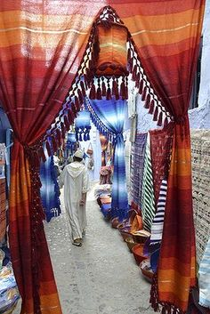 Morocoo. In the medina of Chefchaouen in the Rif Mountains.  The perfect white djellaba is framed by a riot of colours, rugs, fabrics and a thousand things made by hand.