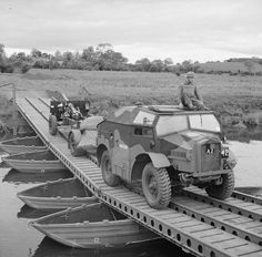 """A 25-pounder field gun and limber being towed by a Morris Commercial """"Quad"""", crossing a pontoon bridge at Slaght Bridge in Antrim, Northern Ireland, 26 June 1942."""