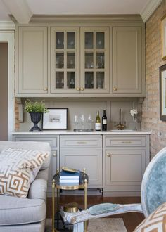 Polished brass accents add a lovely, formal touch to this transitional living room. A built-in bar just steps away from the seating area boasts glass door cabinets that show off beautiful stemware.