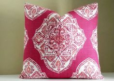 Add drama to your room with a beautifully textured fabric. The decorative medallion print pillow cover is highlighted with white and coral on a magenta
