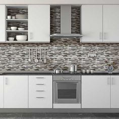 Daltile Endeavors Mosaics blend well with these white cabinets and stainless steel fixtures and accents