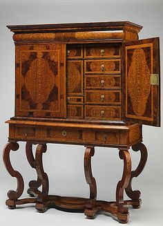 Date: ca. 1700 British Maker unknown  ? Pine veneered with marquetry of walnut, burl walnut, and holly; oak drawers; walnut legs; brass hardware