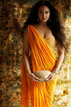 Sonakshi Sinha in an orange saree or sari and blouse complete with a clutch. Love the hair and makeup