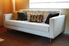 "S&D Ikea Hack Our Mid Century: our karlstad sofa hack. Add 8"" mid century modern legs unstained from Ace Hardware. Stained Early American. Tufted pillows by upholsterer - $40."