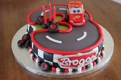 Disney Cars Cake Number three track with Lightning Mcqueen racing aroumd it.