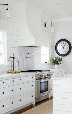 White farmhouse kitchen with shiplap walls.  Love the range vent.