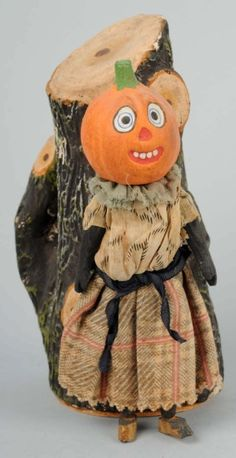 """Description A cloth dressed lady with pumpkin head, contained upon a wire armature body with wooden arms and feet. Standing next to a highly detailed papier mache tree trunk. Lady has huge eyes with chicklet teeth, this piece is reminiscent of the forest scene with the talking apple trees from the Wizard of Oz. Condition (Near Mint). Size 6"""" T."""