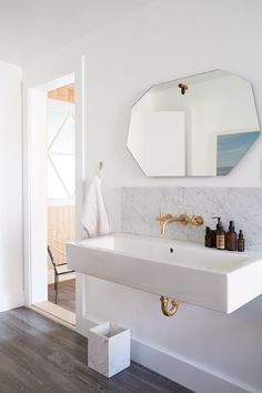 Brass and marble accents, a large wall-mounted sink, and a geometric mirror create a serene bath retreat. #dwell #modernhomesforsale #moderncalifornianhomes #bolinas