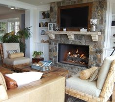 This is what we should do with the fireplace in the family room.  But I want to know what they do with the dvd player and game system....  tropical living room by Dana Nichols