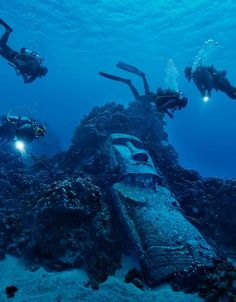 Tourists diving on Easter Island's reef encounter a fake moai, made for a 1994 Hollywood movie and then sunk offshore. - photo by Randy Olson, via National Geographic (This cropped photo is from a different site.)