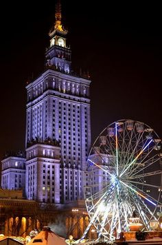Winter night, Palace of Culture and Science, Warsaw (Warszawa), Poland. Lit up in vibrant purple hues, this structure makes a marked contrast against the pitch-black night sky.