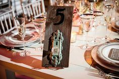 DIY Table Numbers - All you need is 3 things: Piece of wood, vintage lock, and a number. Number can be hand written or purchased (this one was a house number you can buy at a place like Lowes or Home Depot #tablenumber #diy #tabledecor #wedding