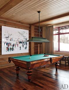 a massimo vitali photograph hangs behind an antique pool table restored by  blatt billiards in the