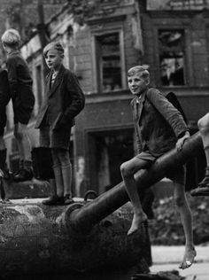 Children play on the bomb sites and wrecked tanks in Berlin, in the aftermath of the fighting in the city, 1945