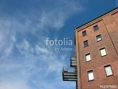 Blauer Himmel mit Wolken über einem sanierten Speicher mit modernen Balkons am Hafen in Münster in Westfalen