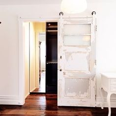 DIY sliding barn door hardware: We installed this door on a 2 inch wide track ( it's $12 to make) and we painted it WHITE.  Amish made wooden wheels on the blog.