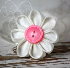 Dainty Daisy white daisy style kanzashi flower is perfect for spring & summer attire.   The daisy flower is finished with a pink button center and secured to an alligator clip for wear in your hair, clipped to your lapel, headband, purse or more.  Looking for something a little dif...