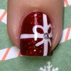 """🎥Tutorial for easy bow nails🎁 I used straight tape from @teismom for the vertical stripe and a brush from @stylishnailartshop for the rest✨ The gorgeous sparkly red base polish is """"He's With Me"""" from @salonperfect, and my topcoat is Seche Vite💋 🎤Song: Kelly Clarkson """"White Christmas""""❄️"""