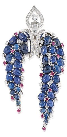 BULGARI - AN ART DECO SAPPHIRE, RUBY AND DIAMOND CLIP BROOCH, CIRCA 1930. The central brilliant and baguette-cut diamond openwork panel of Arabesque design, suspending two trailing cluster panels of cabochon sapphires interspersed with brilliant-cut diamo