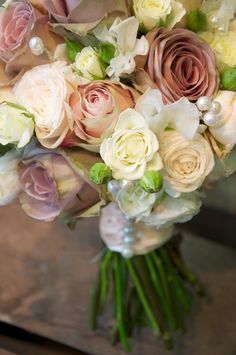 Amnesia roses combined with Bombastic spray roses scented ivory sweet peas, ivory Majolika spray roses, Upper Secret roses, subtle hints of eucalyptus and wired pearls, nestled between the flowers. The #bridalbouquet was bound in a ruched nude satin ribbon, with large pearls lining the length. www.greenparlour.com