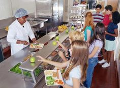 Woman serving food to schoolchildren (10-13) in cafeteria - Baerbel Schmidt / Stone / Getty Images