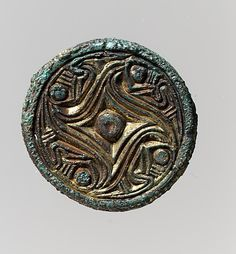 Disk Brooch,  circa 600-500, Vendel, copper alloy, gilt. This brooch is from the Vendel period in Swedish history, which precedes the Viking age. Abstractly designed small brooches like these were fashionable until Viking oval brooches replaced them.