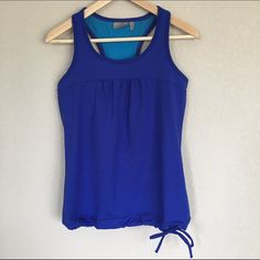 "Cobalt Built-in Bra Tank | Athleta Gently used tank in excellent condition with no imperfections. Beautiful bold blue color with a built-in bra and drawstring on waist so it stays put during yoga and workouts. Fabric is polyester, Lycra spandex and rayon. Wash cold, tumble dry low. Flat measurements: Bust 15"" and bottom hem stretches to 19"". Athleta Tops Tank Tops"