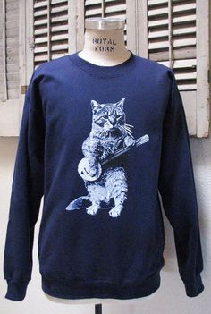 This cat can jam!    This banjo design sweatshirt is printed on soft fabric with environmentally friendly water based ink that sets in the