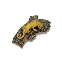 18 KARAT GOLD, SILVER AND RUBY LIZARD BROOCH, BUCCELLATI The three-dimensional reptile of textured gold crouched upon a tree of textured silver, the eyes set with 2 cabochon rubies, signed Buccellati.