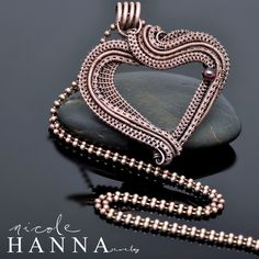 This wire wrap heart pendant is boisterous and full, with many yards of hand coiled, wrapped and woven copper wire layered purposefully in a heart shape, revealing texture and depth. The copper wire has been oxidized to emphasize the attention to detail, and a small garnet accents the finished pi...