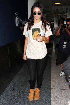 Arriving at LAX in a John Lennon tee paired with black leggings and Timberland boots