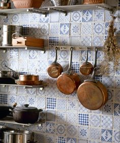 Copper pans hanging on blue tiled wall