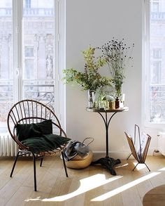 Cozy nook with a rattan chair, a round sidetable and a newspaper rack. Great summery and airy atmosphere due to the flowers.