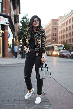 Carolina Hellal of Chic Talk wearing a VIPme floral bomber jacket, Madewell dark gray ripped jeans, h&m white sneakers, and Ralph Lauren striped bag