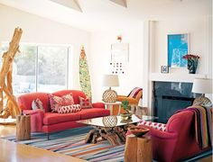 Colorful rug in bold living room with red sofas