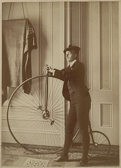 Frances Benjamin Johnston, full-length self-portrait dressed as a man with false moustache, posed with bicycle