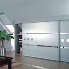 Armarios de diseño a medida con puertas correderas bajo buhardilla.