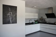 BRUUN interieurontwerp -  Complete make-over, luxe appartement te Elst.   Strakke witte keuken met een prachtig smal werkblad er op. Door het zwart uit de keuken terug te laten komen in de kunst, betrek je de twee vertrekken bij elkaar.